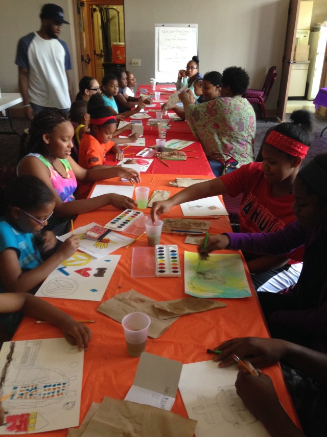 Community volunteers and artists, Mary Watkins and Dominique Coleman, work with campers on their watercolor paintings during a summer camp in June.